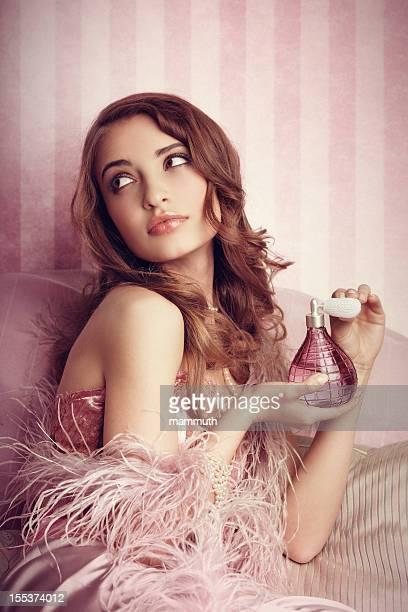 Giovane donna applicando il profumo