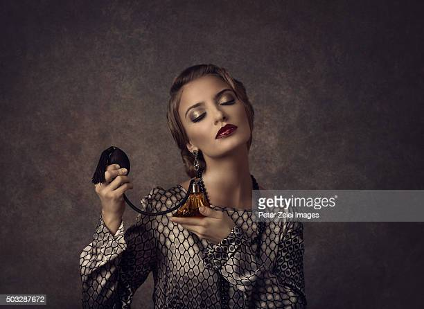 Young woman applying perfume, vintage style image