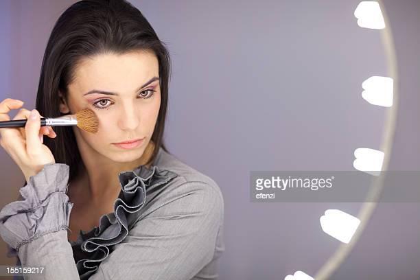 Jeune femme application de poudre dans un miroir de maquillage