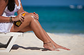 Young woman applying sunscreen on legs in a beach