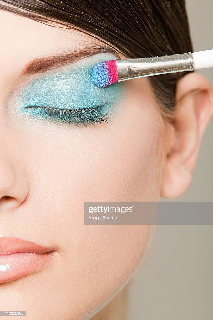 Young woman applying turquoise eyeshadow
