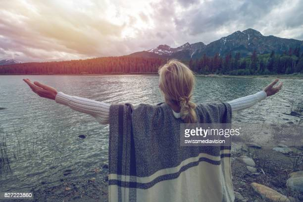 Young woman arms outstretched by the lake