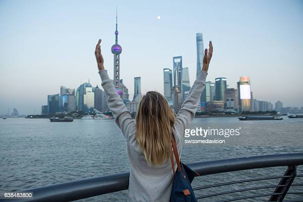 Young woman arms outstretched in Shanghai, China