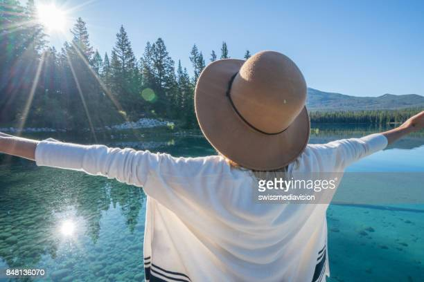 Young woman arms outstretched on lake pier at sunrise