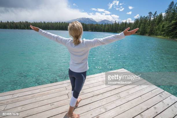 Young woman arms outstretched on lake pier