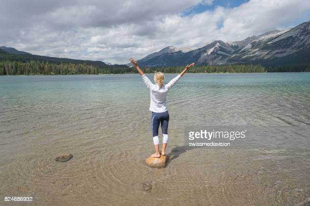 Young woman arms outstretched on rock above lake