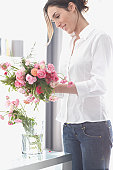 Young woman arranging bunch of flowers in vase, smiling