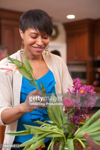 Young Woman arranging flowers in vase : Stock Photo