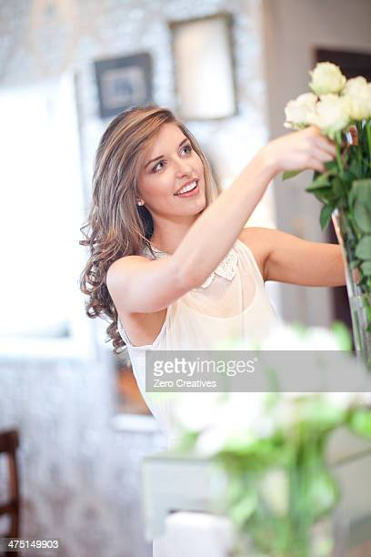 Young woman arranging roses in vase