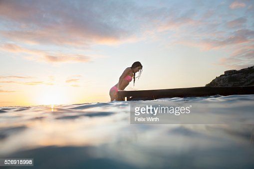 Young woman ascending wooden pier at sunset : Stock-Foto