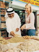 Young Woman Asking a Market Trader About Spices in a Sack at a Souk in Dubai