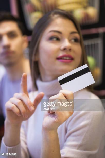 Young woman asking to make a payment with credit card