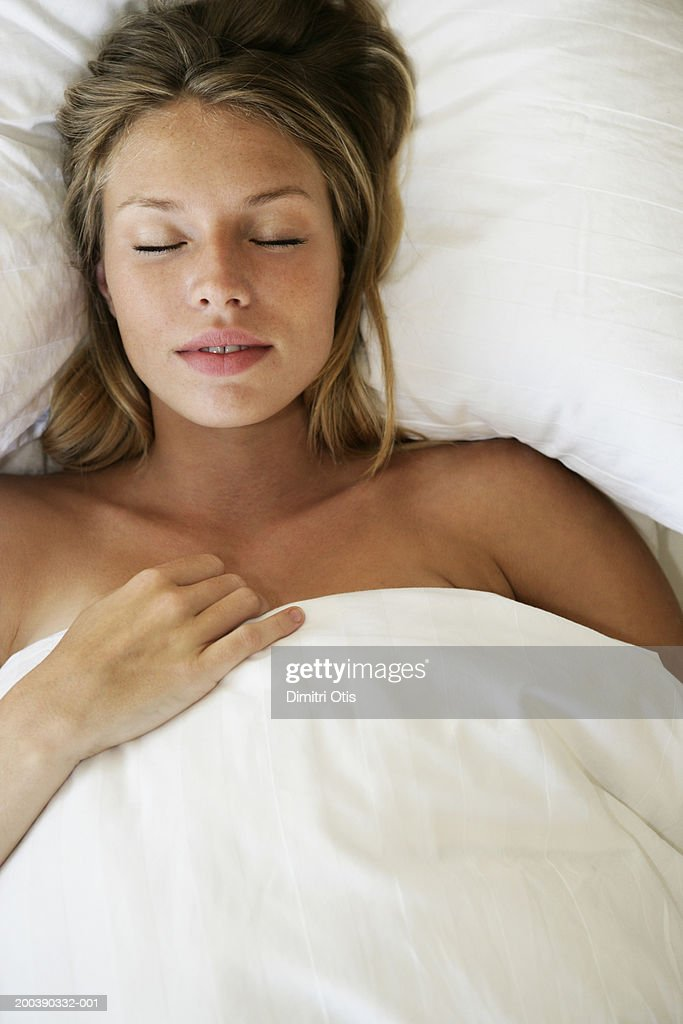 Young woman asleep in bed, elevated view, close-up : Stock Photo