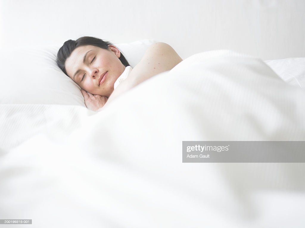 Young woman asleep in bed : Stock Photo
