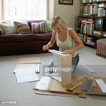 Young Woman Assembling Flatpack Furniture In Her Living Room Stock Photo