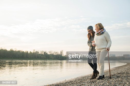Young woman assisting her grandmother walking