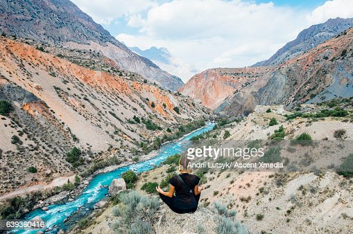 Young woman assumes yoga stance above river, canyon