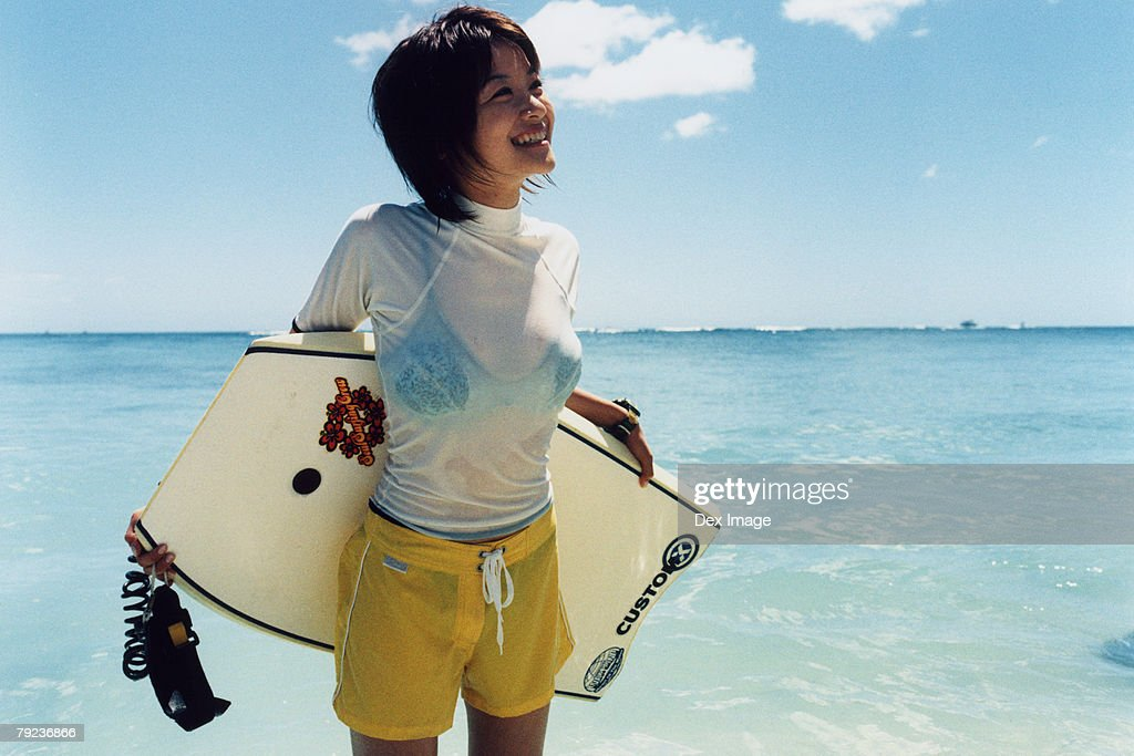 Young woman at a beach, holding paddleboard : Stock Photo