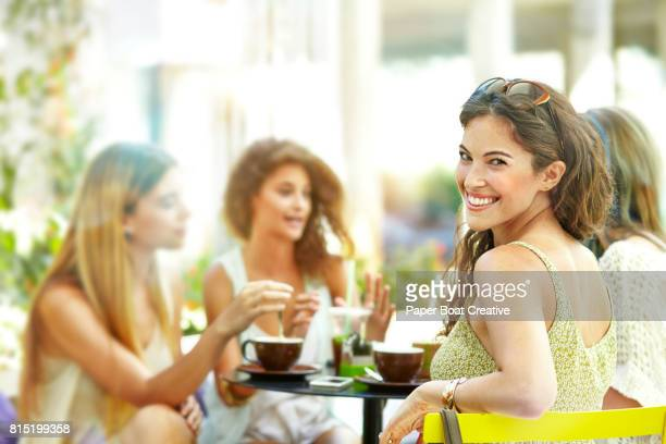 young woman at a cafe turning around to face the camera