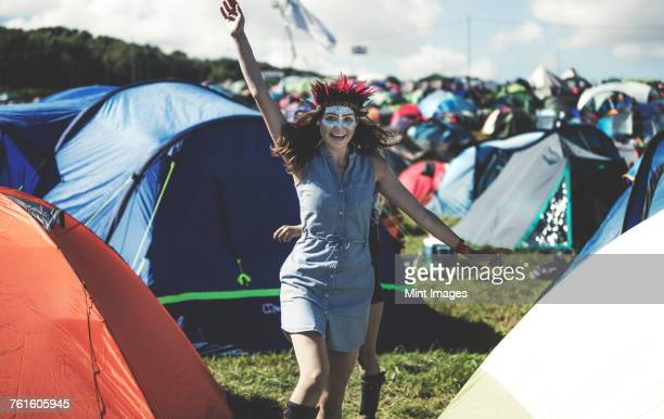 Young woman at a summer music festival face painted, wearing feather headdress, standing near the campsite surrounded by tents, arm raised, smiling.