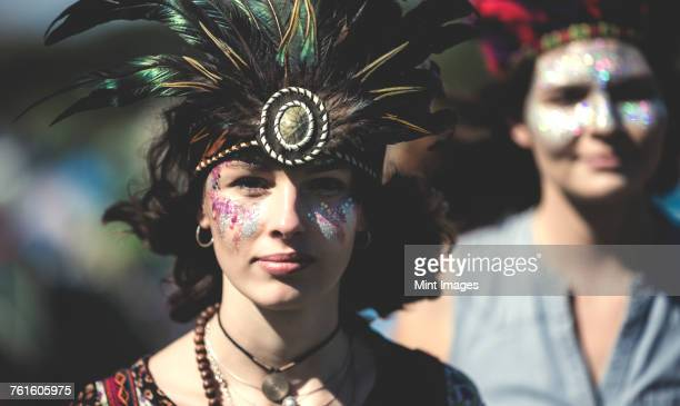 Young woman at a summer music festival face painted, wearing feather headdress, looking at camera.
