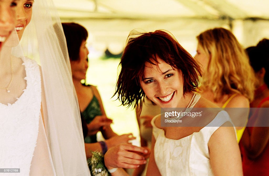 Young woman at a wedding party with other people in the background : Stock Photo