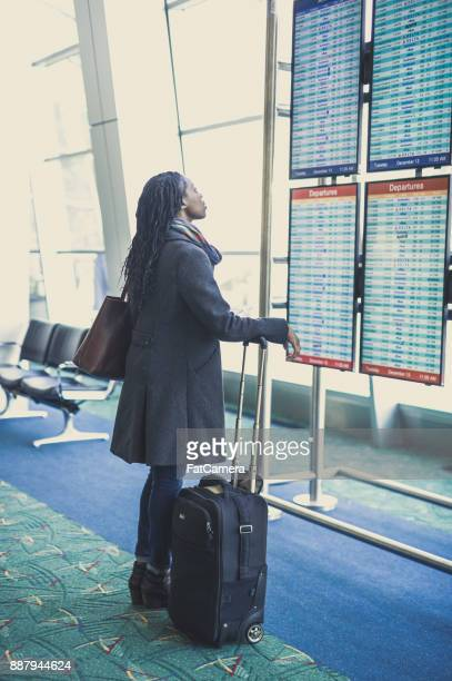 Young woman at airport checking departures board.