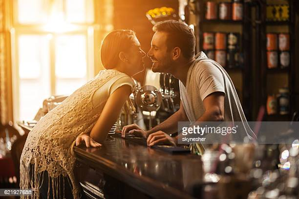 Young woman at bar counter about to kiss smiling bartender.