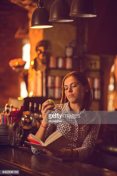 Young woman at bar counter reading a book.