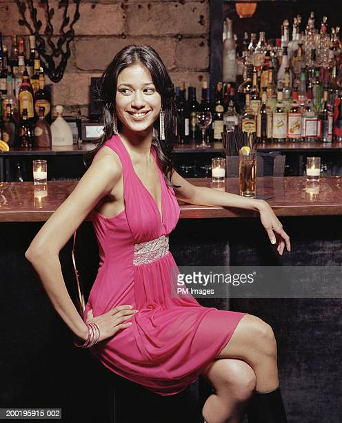 Young woman at bar in nightclub, smiling