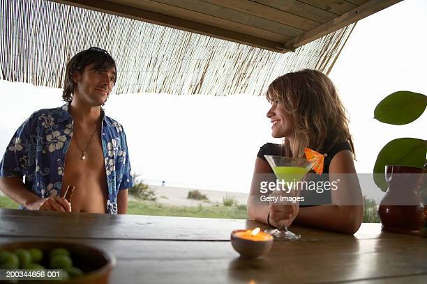 Young woman at beach bar, smiling at man with open shirt