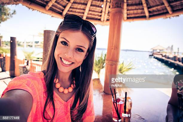 young woman at beach club, taking selfie