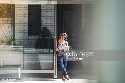 Young woman at bus stop reading newspaper and waiting for bus, New York, US
