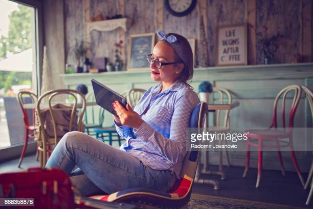 Young woman at cafe using digital tablet