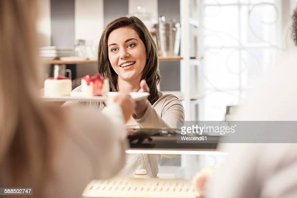 Young woman at cake counter serving cake to clients