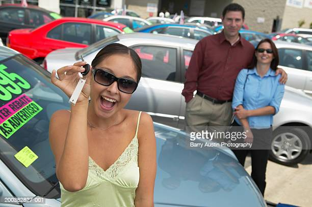 Young woman at car lot, holding keys, parents in background, portrait