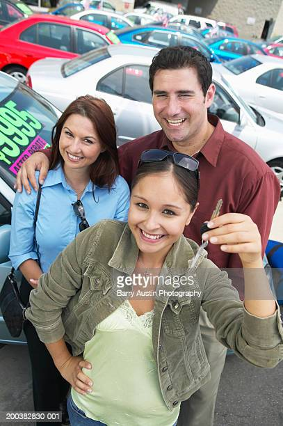 Young woman at car lot with parents, holding keys, portrait