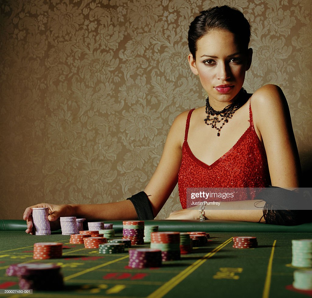 Young woman at casino table holding pile of gambling chips, portrait : Stock Photo