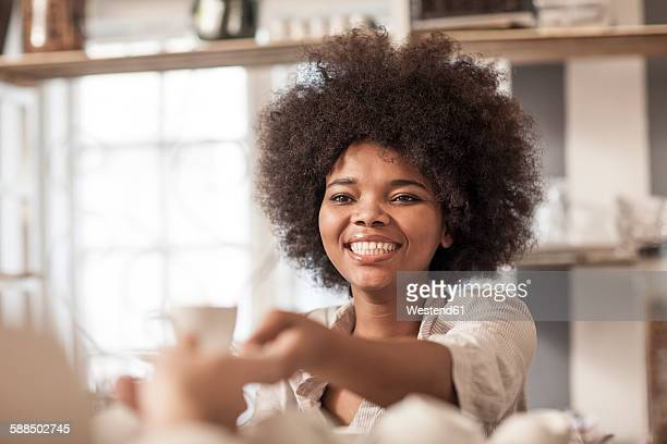 Young woman at coffee bar serving coffee to client