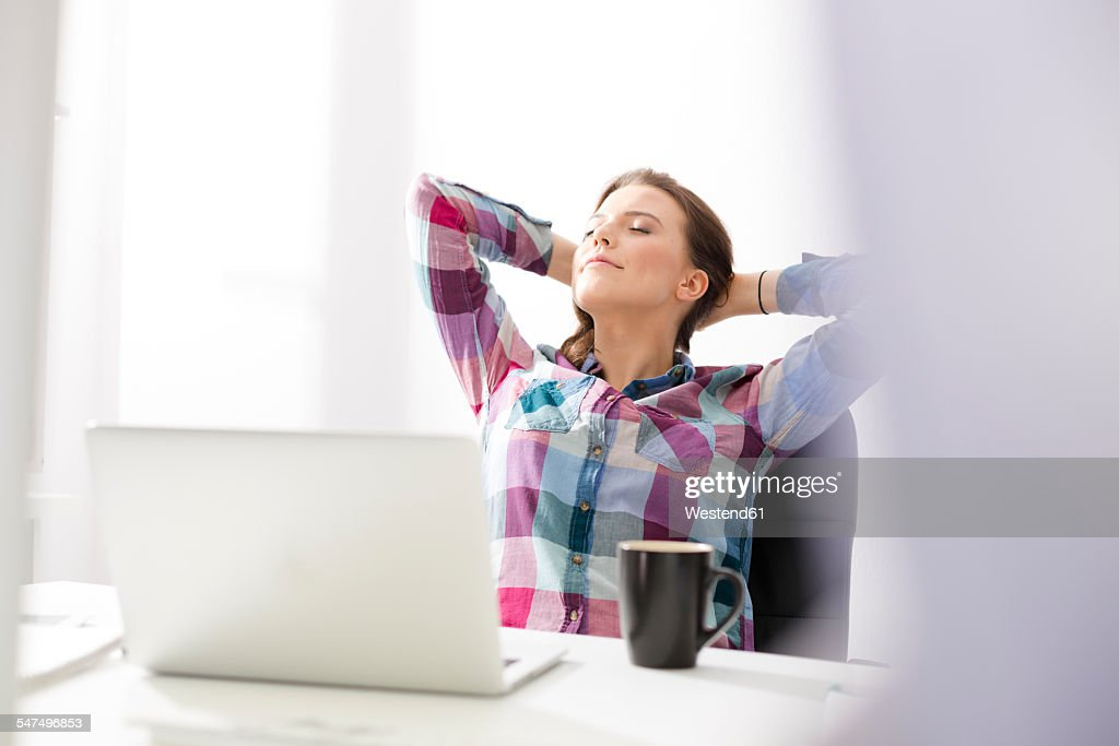 Young woman at desk leaning back