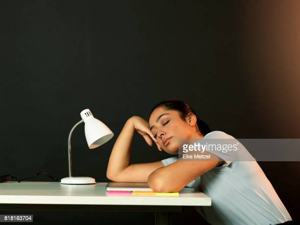 young woman at desk with her eyes closed