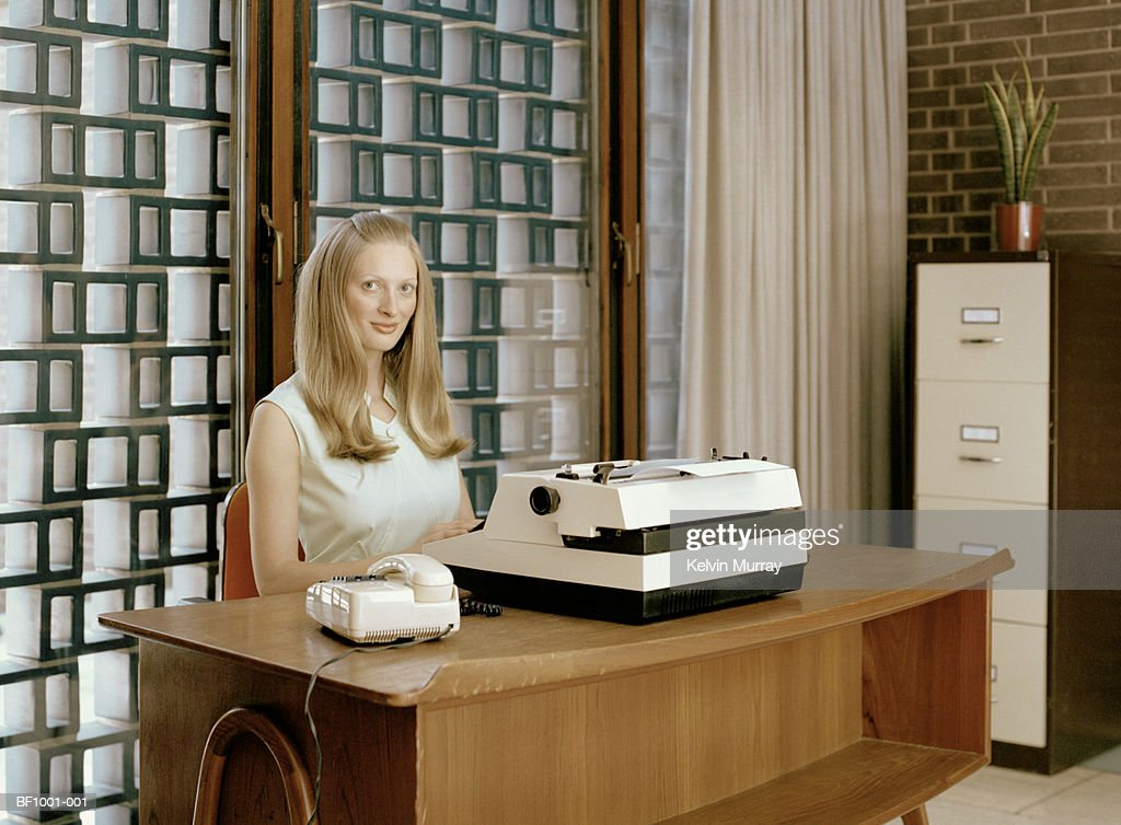 Young woman at desk with typewriter, portrait