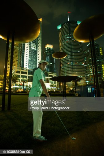 Young woman at financial district playing golf, night (digital composite)