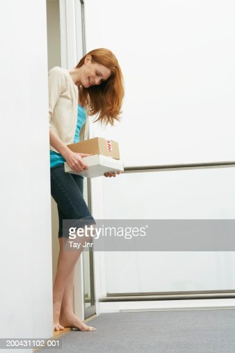 Young woman at front door holding parcels, smiling, side view : Stock Photo