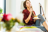 Young woman at home enloying piece of cake in bed