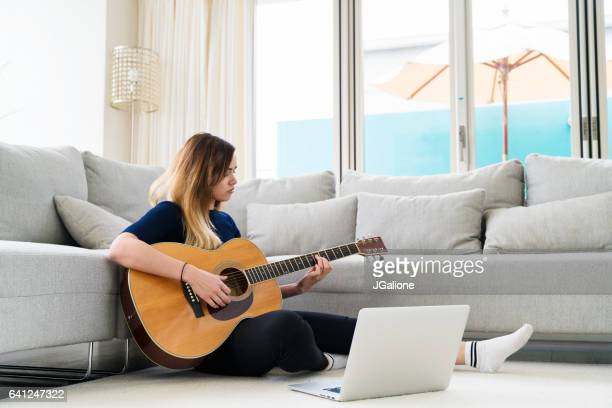 Young woman at home playing the guitar