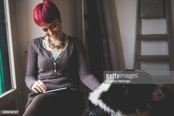 Young woman at home using digital tablet, stroking dog