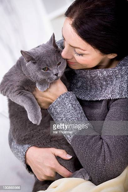 A young woman at home with a British Shorthair cat