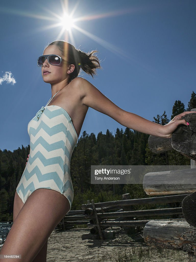 Young woman at mountain lake with lens flare : Stock Photo