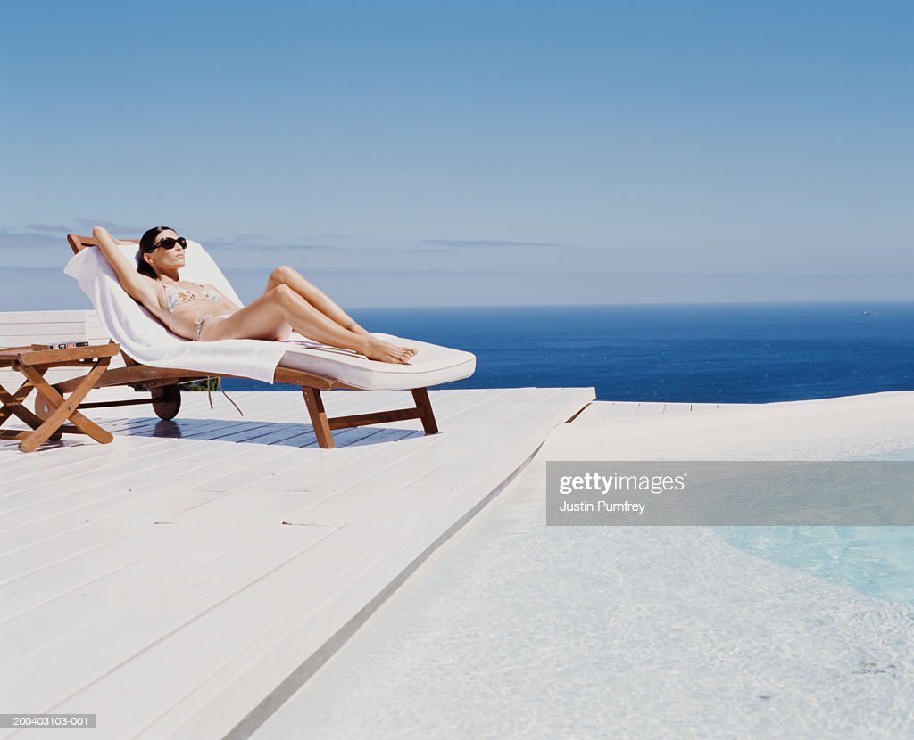 Young woman at spa relaxing on sunlounger by outdoor pool : Stock Photo